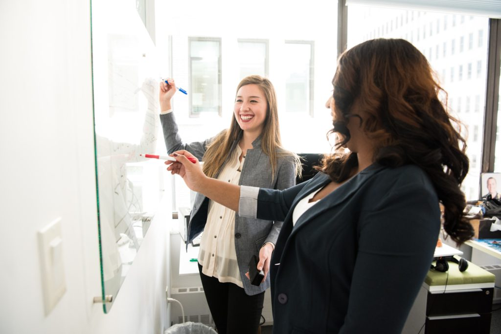 two women in front of dry erase board 1181533