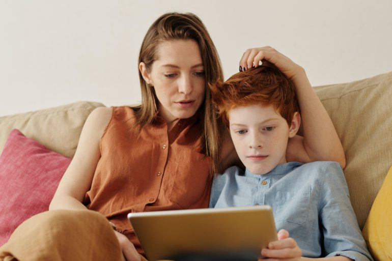 photo of woman and boy watching through tablet computer 4145349