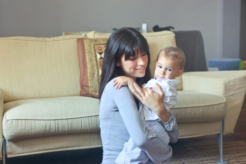 woman in gray sweater carrying toddler in white button up 755049